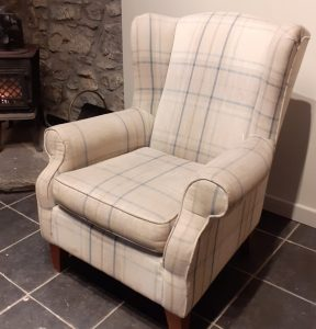 pale check wingback chair in a dirty condition